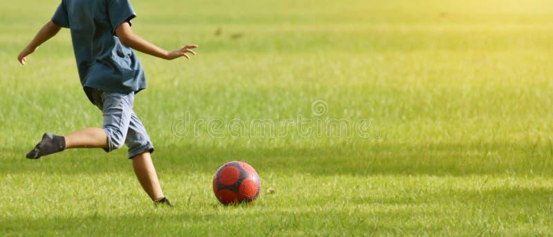 Los muchachos asiáticos, pie de la elevación se preparan para golpear el balón de fútbol con el pie como strengt imagen de archivo libre de regalías