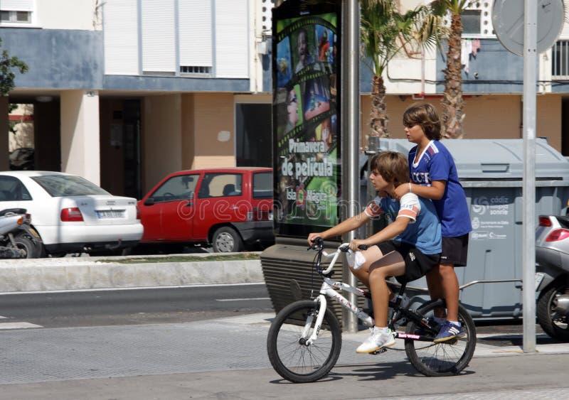 Los muchachos desconocidos montan una bici a lo largo de la calle imagenes de archivo