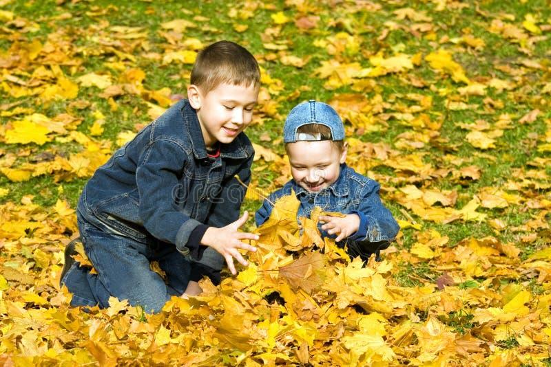 Los muchachos en parque del otoño imagenes de archivo