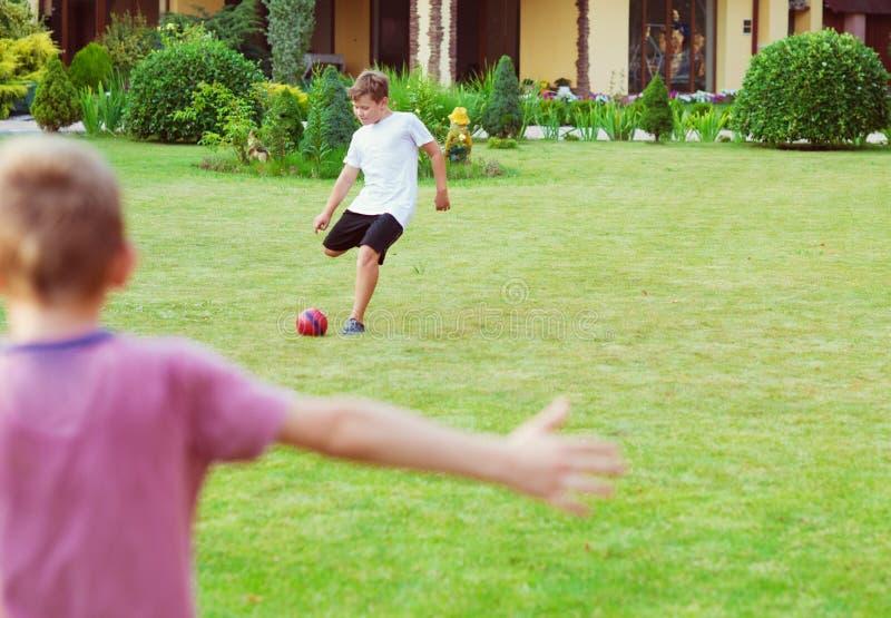 Los muchachos felices que juegan a fútbol en schoolgarden imagen de archivo
