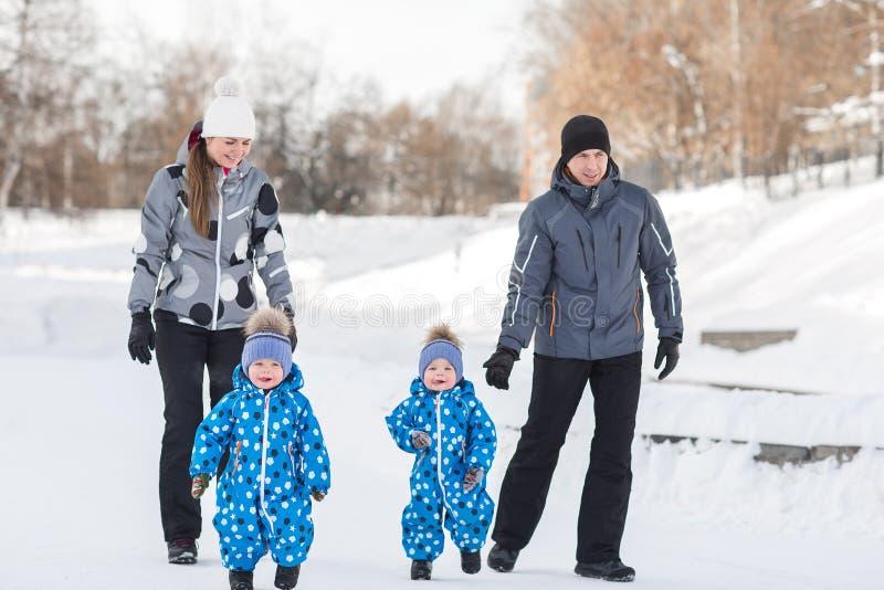 Los muchachos gemelos que caminan en el invierno, padres están volviendo fotos de archivo