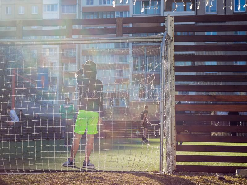 Los muchachos juegan en el patio en un campo de fútbol especialmente equipado en el fondo de las construcciones de viviendas imagenes de archivo