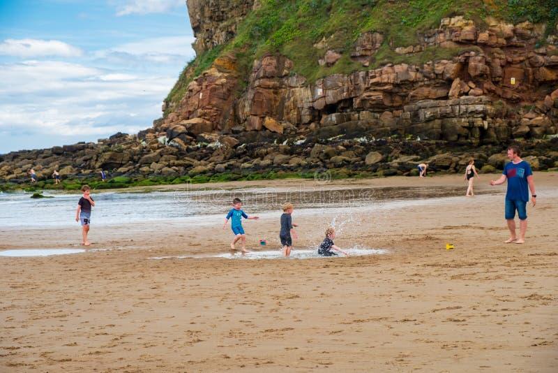 Los muchachos que juegan en la bahía del ` s de rey Edward varan en un s en parte nublado caliente fotos de archivo