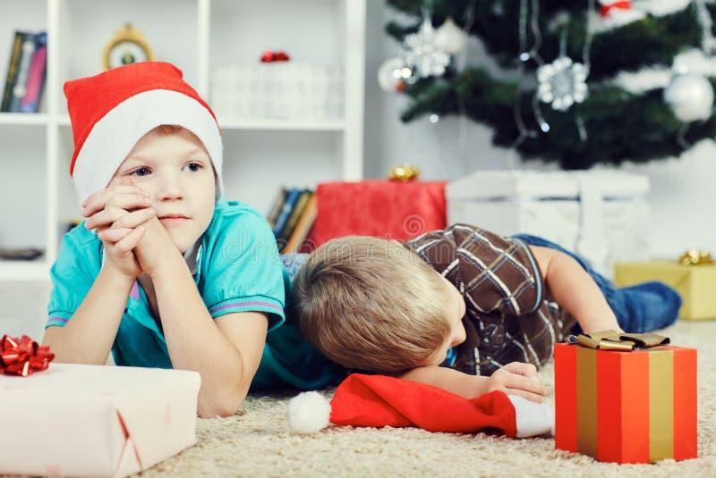 Los muchachos tristes en Papá Noel capsulan esperar el tiempo en que será posible abrir los regalos fotos de archivo libres de regalías