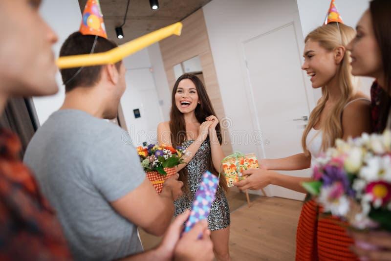 Los muchachos y las muchachas encuentran a la muchacha del cumpleaños con los regalos La muchacha está muy contenta con la sorpre foto de archivo libre de regalías