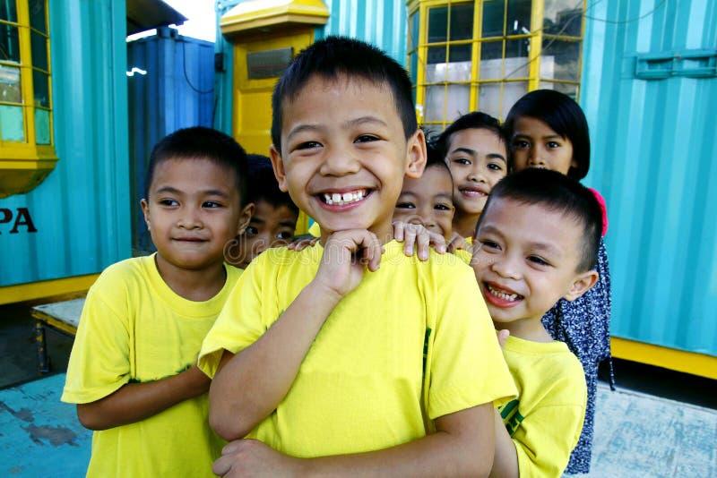 Los muchachos y las muchachas jovenes amontonan y sonríen para la cámara foto de archivo