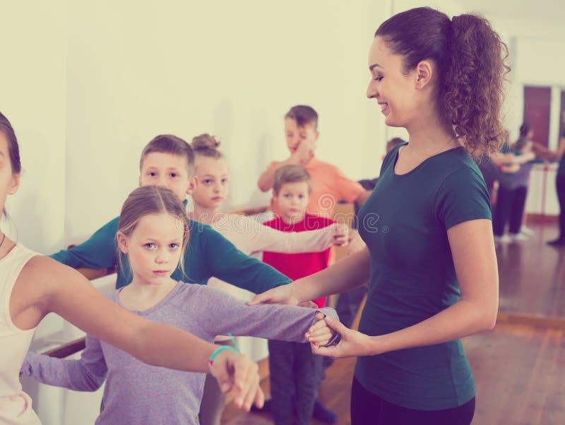 Los muchachos y las muchachas sonrientes que ensayan ballet bailan en estudio imagen de archivo