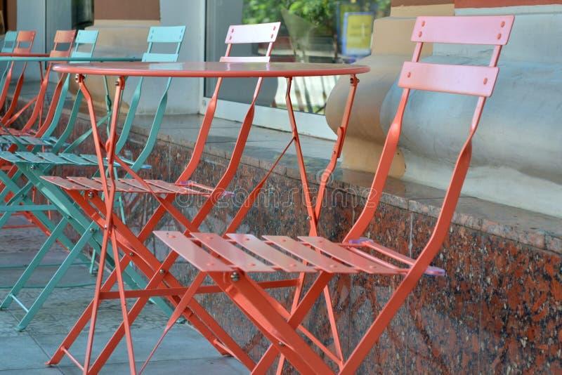 Los muebles del verano hicieron del metal cerca del caf? Primer azul y coralino de las tablas y de las sillas del metal imagenes de archivo