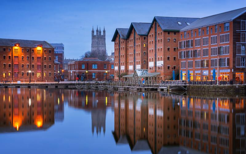 Los muelles y la catedral de Gloucester reflejaron en el muelle en agudeza en el crepúsculo imágenes de archivo libres de regalías