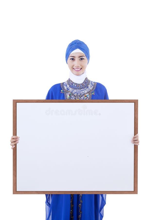 Los musulmanes femeninos asiáticos llevan a cabo el tablero del copyspce - aislado fotografía de archivo