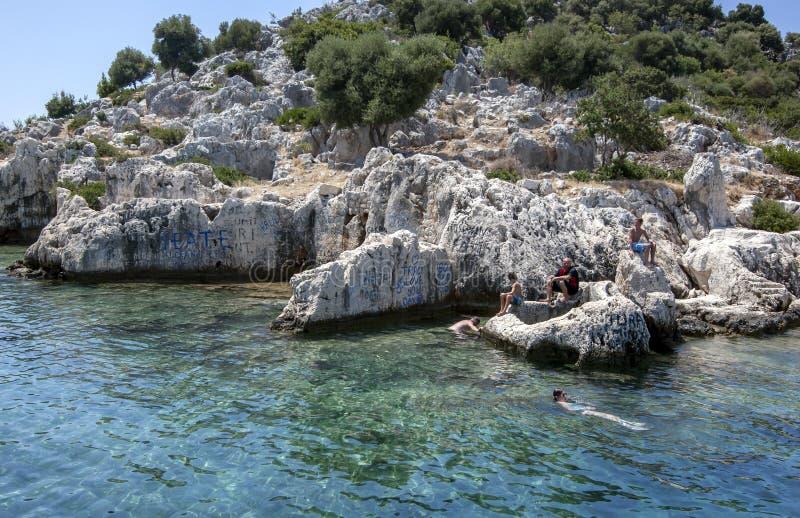 Los nadadores descansan adyacente a la ciudad hundida de Simena en la isla de Kekova foto de archivo libre de regalías