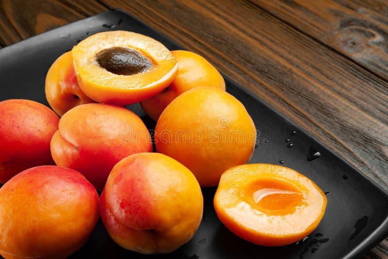 Los nass Aprikosen auf einem nass dunklen Hintergrund Frische saftige rötliche Aprikosen auf einer dunklen Lehmplatte gespritzt m stockbilder