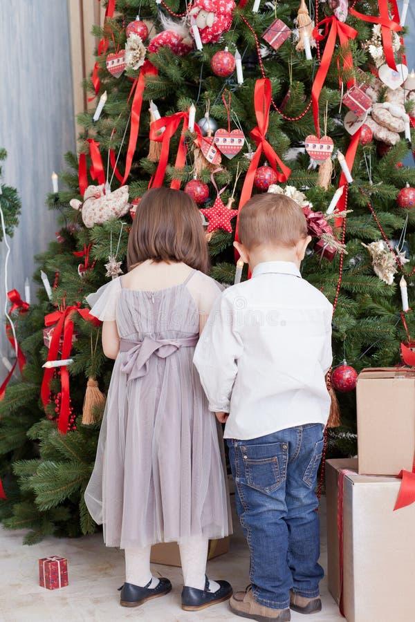 Los niños adornan un árbol de navidad imagen de archivo libre de regalías