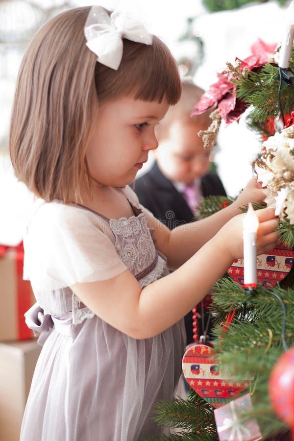 Los niños adornan un árbol de navidad fotografía de archivo
