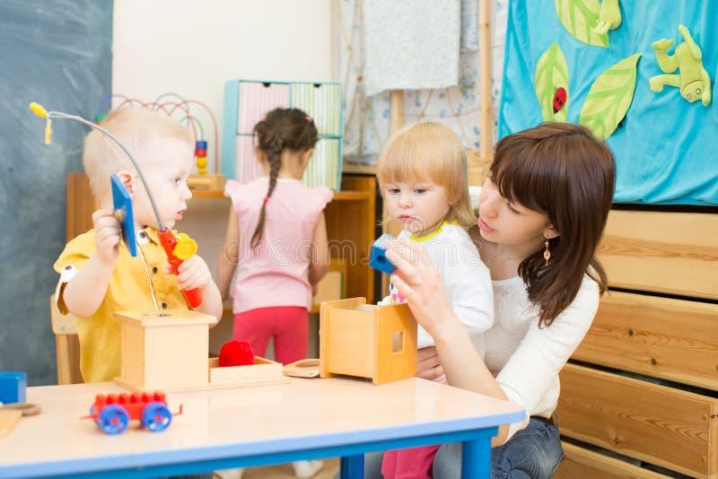 Los niños agrupan jugar con el profesor en sala de juegos del centro de cuidado de día fotografía de archivo