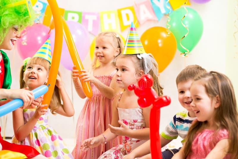 Los niños agrupan y payaso en fiesta de cumpleaños fotografía de archivo