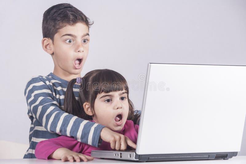 Los niños asustados reaccionan mientras que usan un ordenador portátil foto de archivo libre de regalías