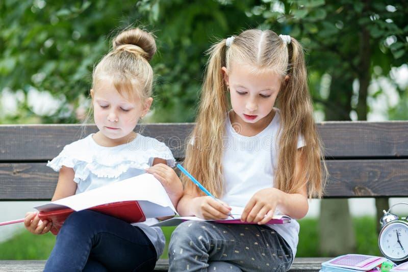 Los niños atentos dibujan en el patio El concepto de escuela, estudio, educación, amistad, niñez foto de archivo libre de regalías