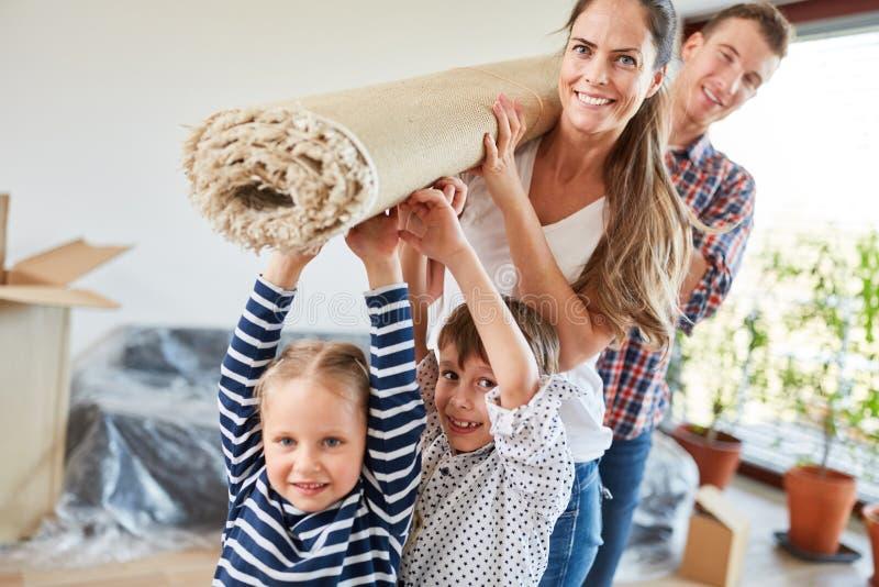 Los niños ayudan a padres a moverse fotografía de archivo libre de regalías