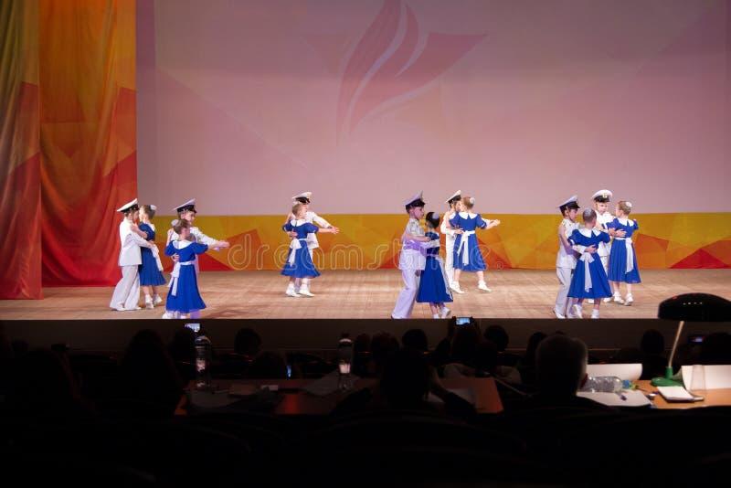 Los niños bajo la forma de marineros militares están bailando el vals en el st imagen de archivo
