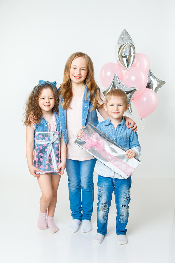 Los niños bonitos en fiesta de cumpleaños permanecen con los presentes en ropa de los vaqueros globos Sonrisa fotografía de archivo