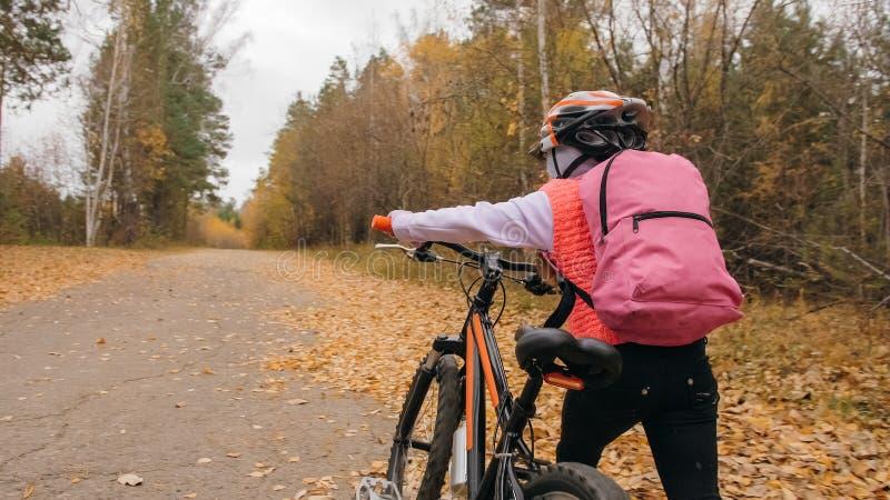 Los niños caucásicos uno caminan con la bici en parque del otoño La niña que camina el ciclo anaranjado negro en niño del bosque  imágenes de archivo libres de regalías
