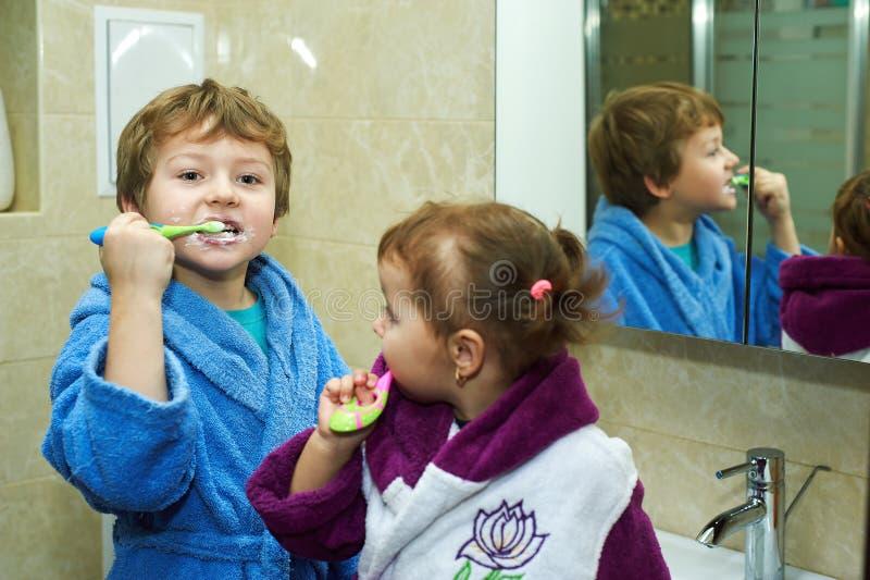 Los niños cepillan su mañana de los dientes en el cuarto de baño, vestido en trajes imagenes de archivo