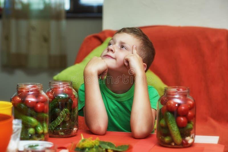Los niños cocinan las verduras para el invierno imagenes de archivo