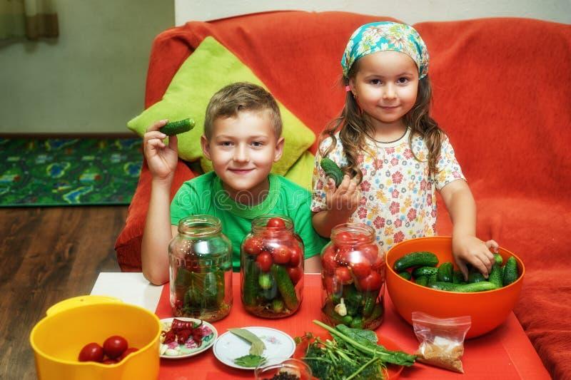 Los niños cocinan las verduras para el invierno Mercanc?as conservadas fotos de archivo