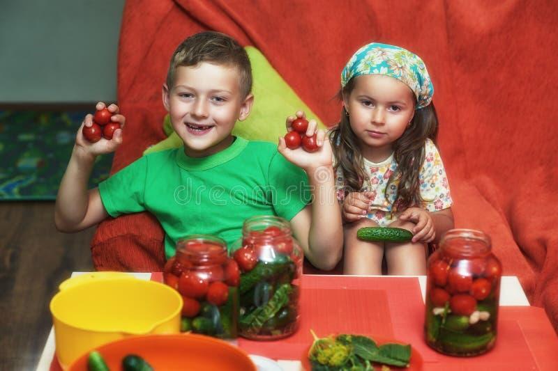 Los niños cocinan las verduras para el invierno Mercanc?as conservadas foto de archivo
