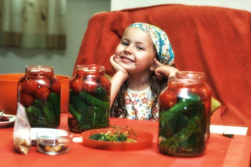 Los niños cocinan las verduras para el invierno Mercanc?as conservadas fotografía de archivo