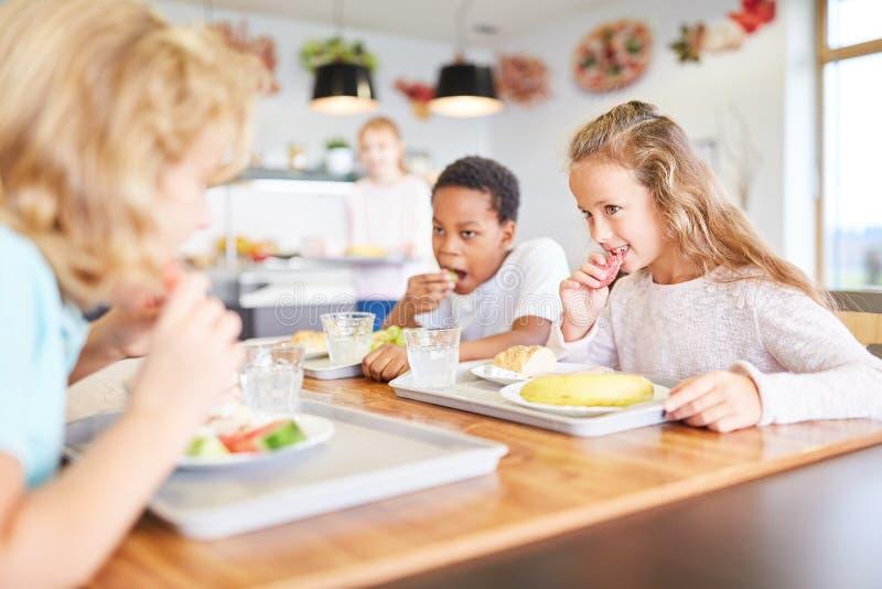 Los niños comen juntos en la cantina foto de archivo