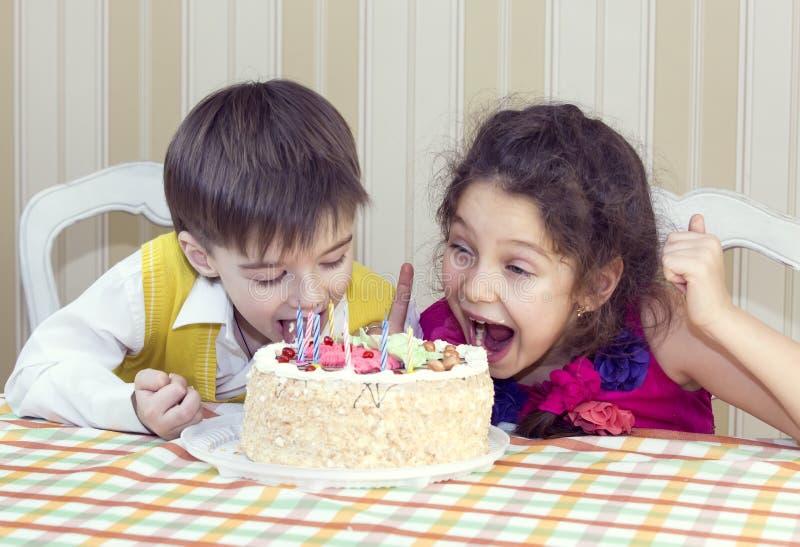 Los niños comen la torta imagen de archivo