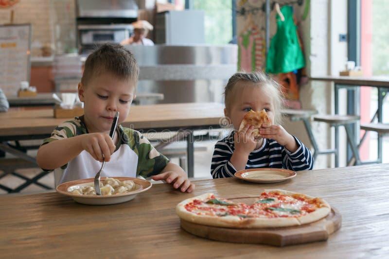 Los niños comen las bolas de masa hervida de la pizza y de la carne en el café niños que comen la comida malsana dentro Hermanos  foto de archivo libre de regalías