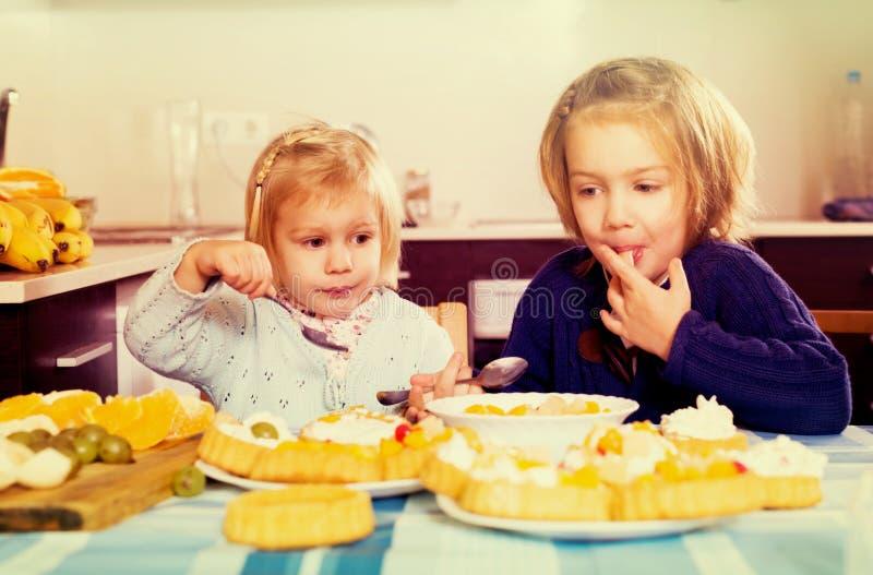 Los niños comen las tortas en la cocina fotos de archivo