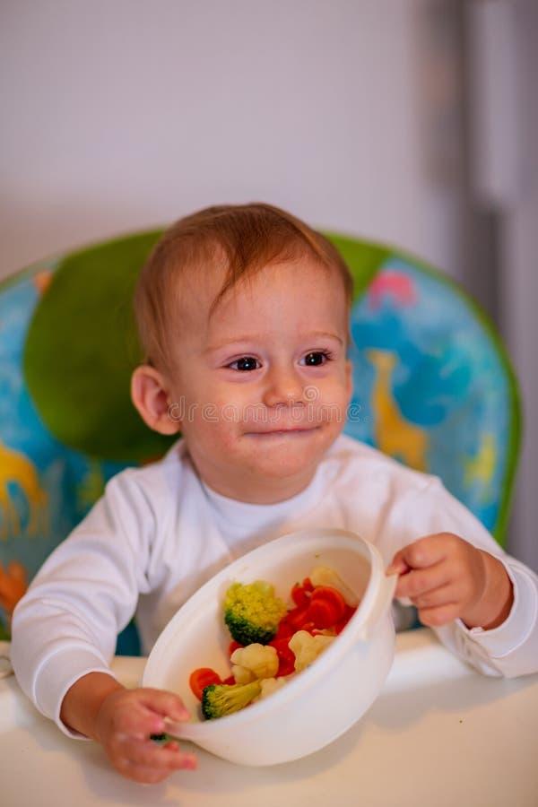 Los niños comen verduras Muchacho feliz que come verduras sanas imagen de archivo