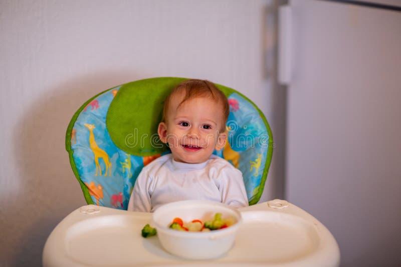 Los niños comen verduras Muchacho sonriente que come verduras sanas imagen de archivo libre de regalías