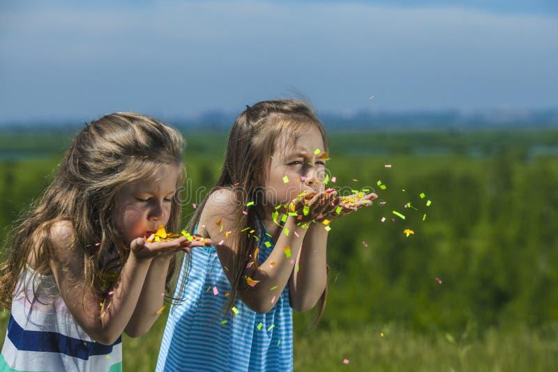 Los niños con confeti a disposición los inflan en el viento imágenes de archivo libres de regalías