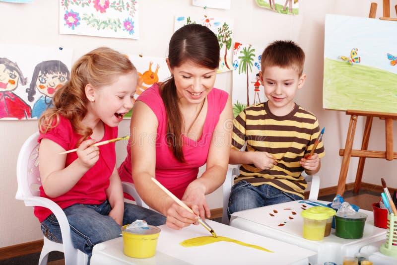 Los niños con el profesor drenan las pinturas en sitio del juego. foto de archivo libre de regalías