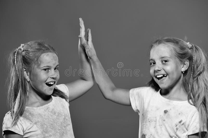 Los niños con las colas de caballo hacen altos fives Muchacha del amigo Las colegialas tienen puntos de la pintura fotografía de archivo libre de regalías