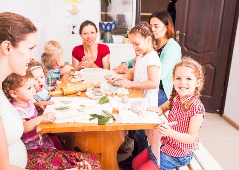 Los niños con las madres son esculpen imagenes de archivo