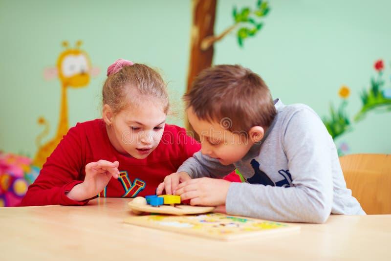 Los niños con necesidades especiales desarrollan su movilidad fina en centro de rehabilitación de la guardería fotografía de archivo