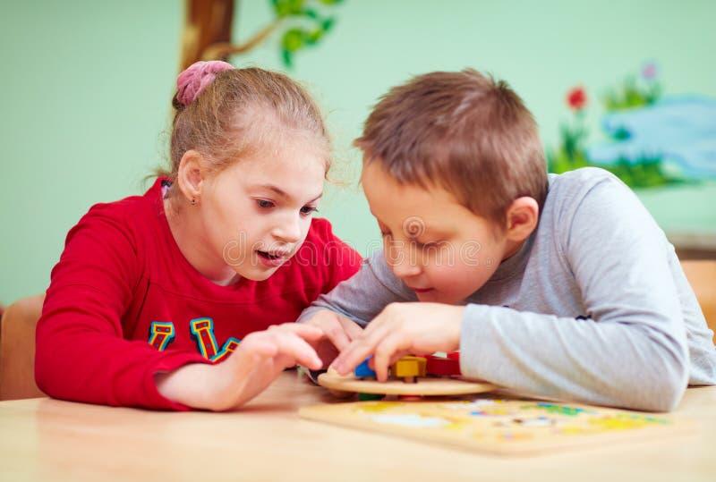 Los niños con necesidades especiales desarrollan sus capacidades finas de motor en centro de rehabilitación de la guardería foto de archivo