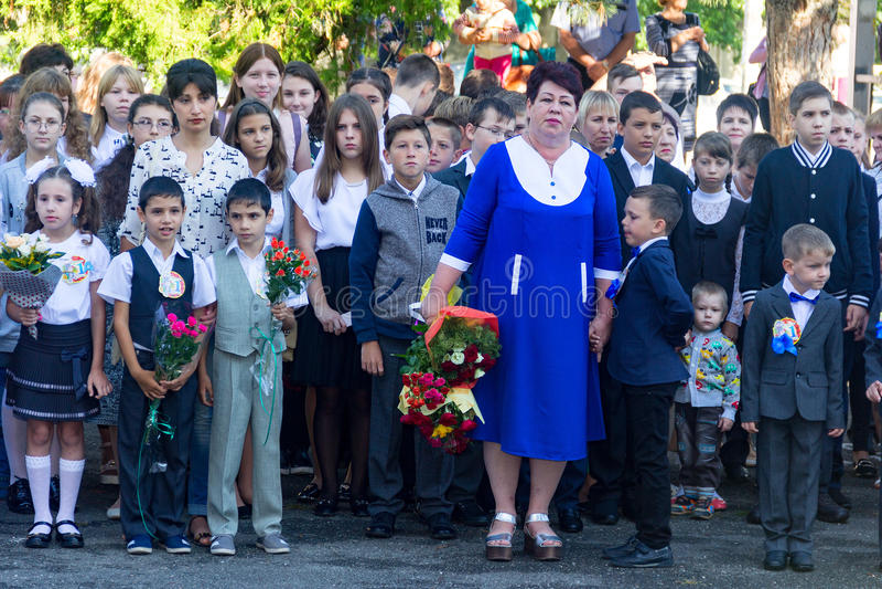 Los niños con los ramos de flores alistaron en la primera clase en la escuela con los profesores y los estudiantes de la High Sch fotografía de archivo