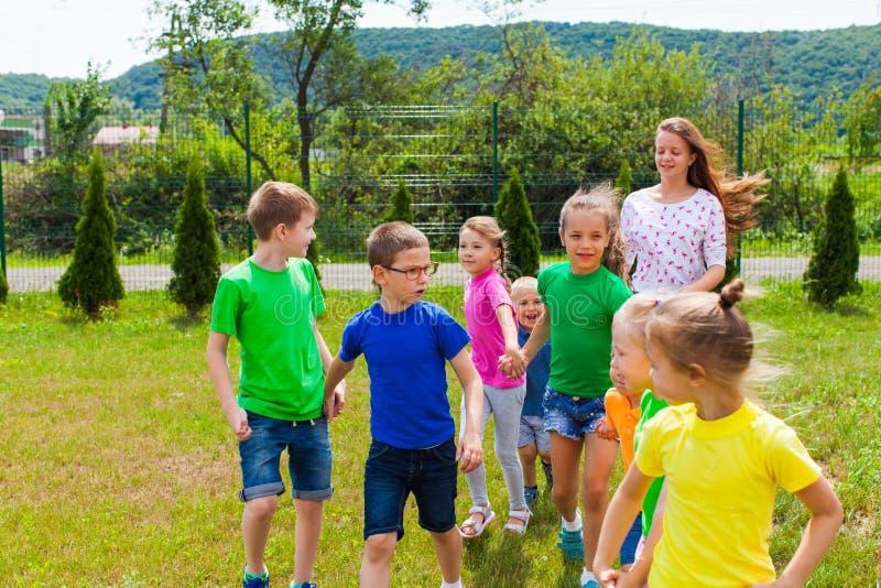 Los niños con tutor van al patio de juegos en el campamento de verano imagen de archivo libre de regalías