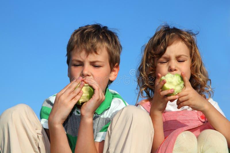 Los niños, contra el cielo comen manzanas verdes fotos de archivo