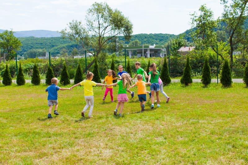 Los niños corren cogidos de la mano en el césped verde fotos de archivo libres de regalías