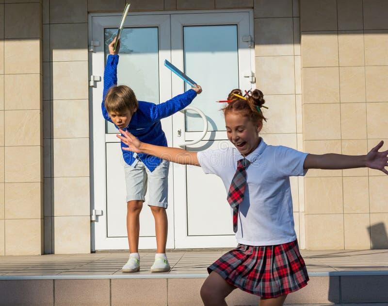Los niños corren feliz de escuela y lanzan para arriba los libros después del en imágenes de archivo libres de regalías