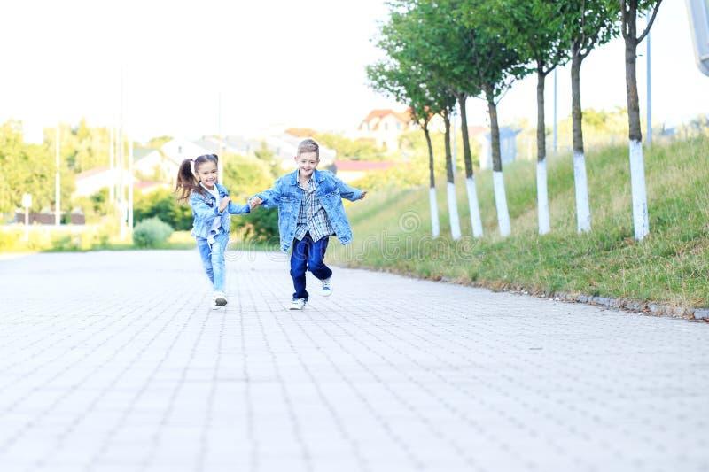 Los niños corren llevar a cabo las manos El concepto de niñez, familia, educación imágenes de archivo libres de regalías