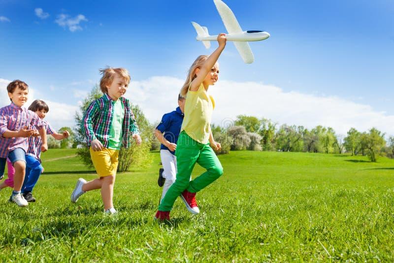 Los niños corrientes y la muchacha que sostienen el aeroplano blanco juegan imagen de archivo